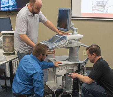Three men inspecting ultrasound machine